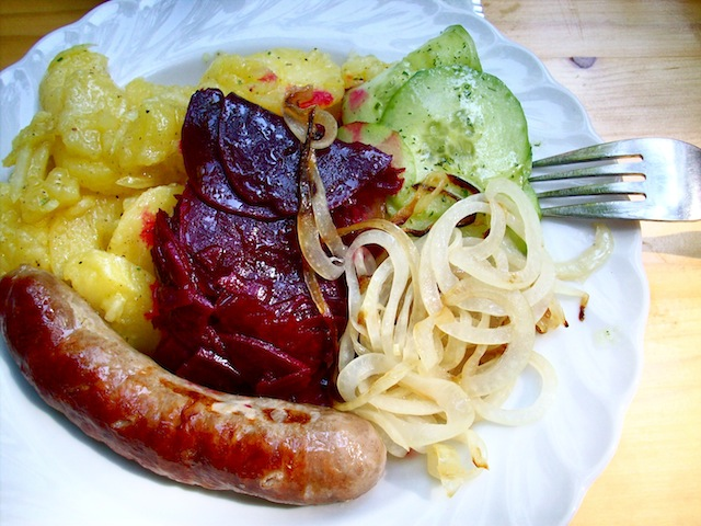 bratwurst with potato salad, beet salad, cucumber salad, and grilled onions (Eat Me. Drink Me.)